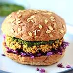 baked samosa burger with red cabbage and coriander mint sauce and bun on blue plate