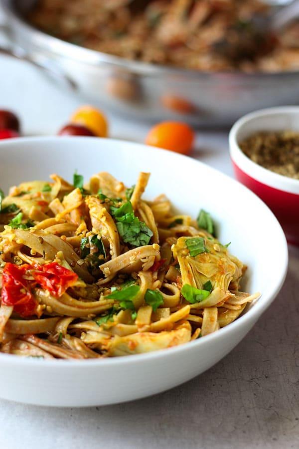 pasta with tomato, artichoke and fresh basil in white bowl