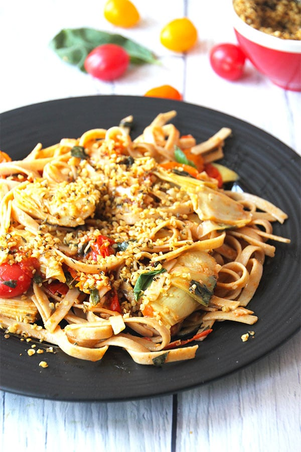 Pasta with tomato, artichoke, fresh basil and hemp seed Parmesan on black plate