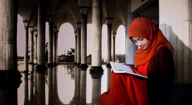 gadis berhijab belajar dengan buku