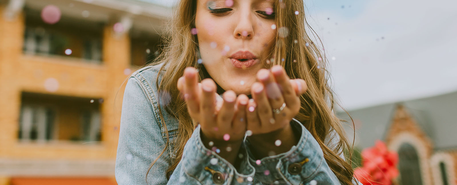 senior high school girl blowing glitter from her hands