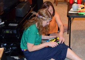 """One of my friends thoughtfully used my camera to record the exact moment I lost my mind. This is my friend Hsing-Yi showing me how to play the game. I am dressed for a 60s party and I elieve my T-shirt reads """"All we are saying, is give peace a chance."""" Bop it!"""
