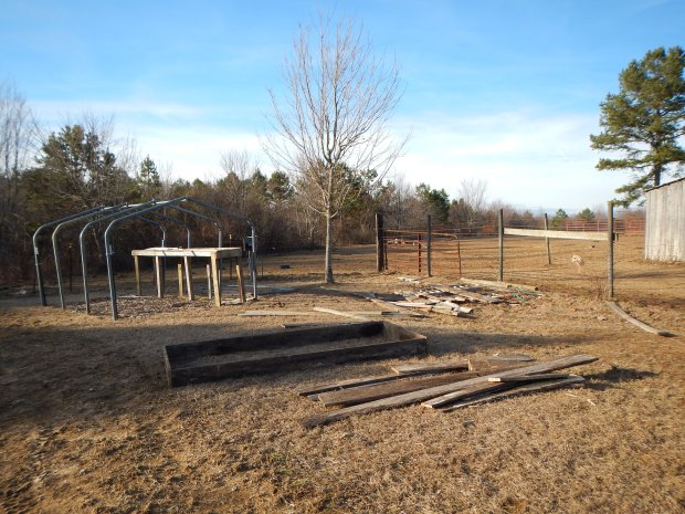 Raised bed with scrap wood pile and recycled garage frame that is going to be built into a greenhouse, Grundy County Community Garden, White City, Tennessee