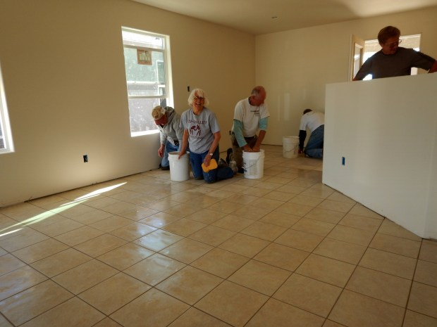 Mary Jo smiling while cleaning tiles after grouting, Mesilla Valley Habitat for Humanity, Las Cruces, New Mexico