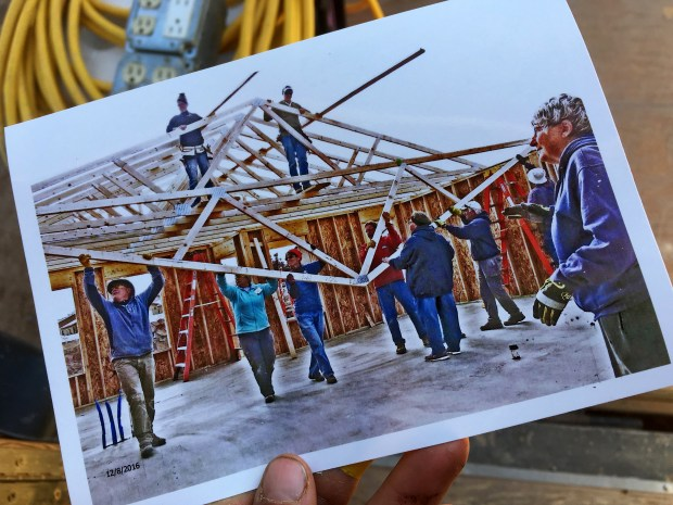 Print of a photo taken by local volunteer Mac. This shows a truss being swung up while Pete and I are standing in the rafters
