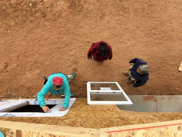 Paula, Brenda, and Lee installing windows