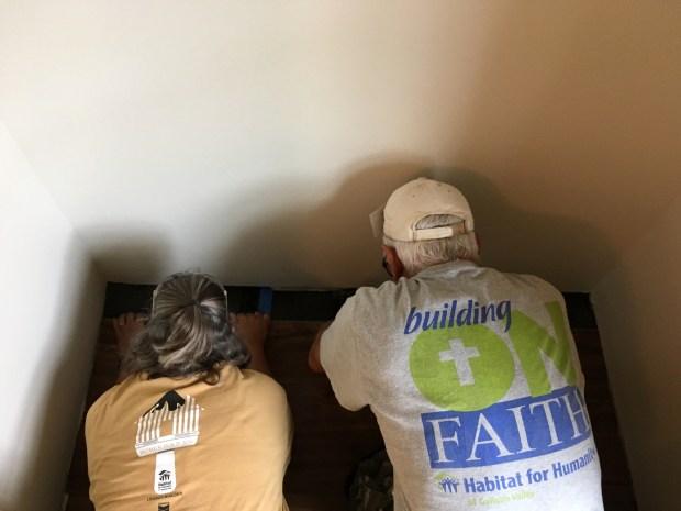 Sandi and Tom installing flooring in a bedroom closet