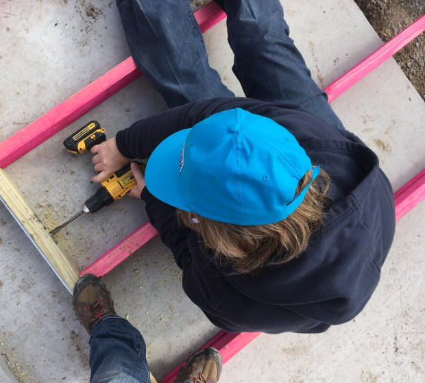 Helen drilling holes in the bottom plate for the anchor bolts