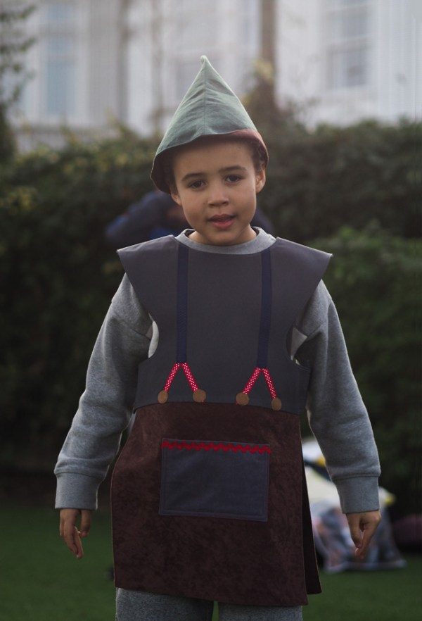 A boy wearing the woodcutter tabard and hat