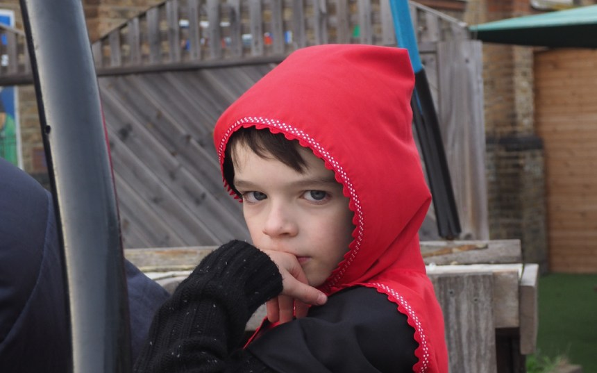 Head and shoulder shot of a white boy in a red hooded cape