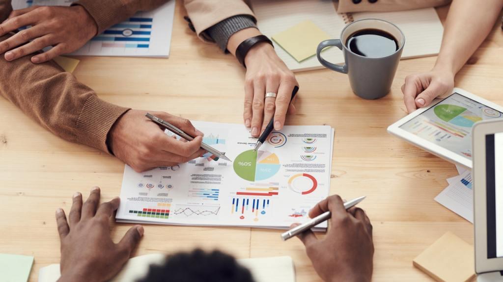 Riunione in ufficio, persone alla scrivania valutano grafici su quanto deve incidere il costo del personale sul fatturato
