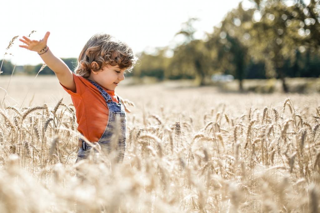 Bambino che corre in un campo di grano in estate
