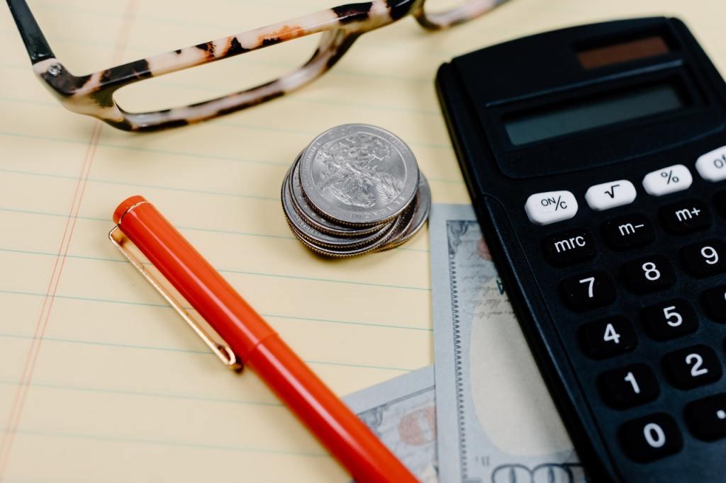 Scrivania con calcolatrice, penna, monete, occhiali