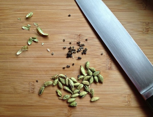green cardamom pods on cutting board with knife