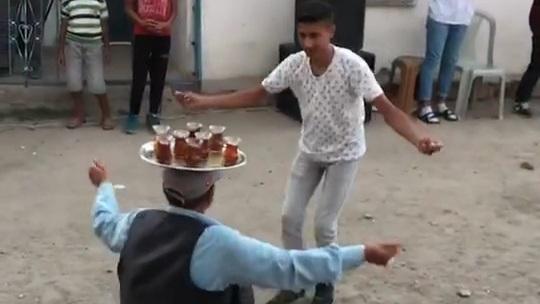 Başının üstünde çay tepsisi ile oynayan adam