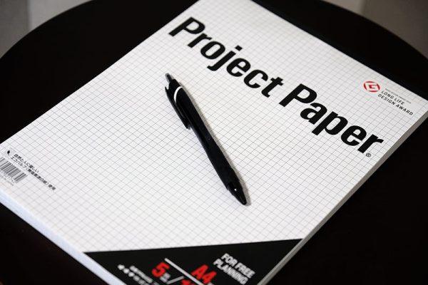 ロゴデザインの時に使用する方眼紙とボールペンの写真