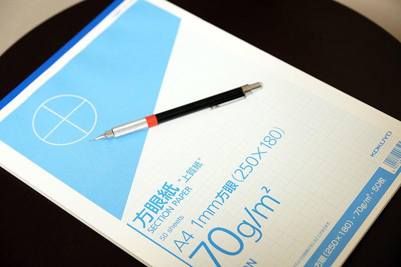 ロゴデザインの時に使用する細かい方眼紙とシャーペンの写真