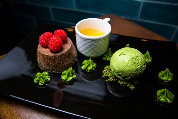 Фондант с белым шоколадом, украшенный фисташковым тюилем в тандеме с мороженым из чая матча и соусом из пюре манго и маракуйи