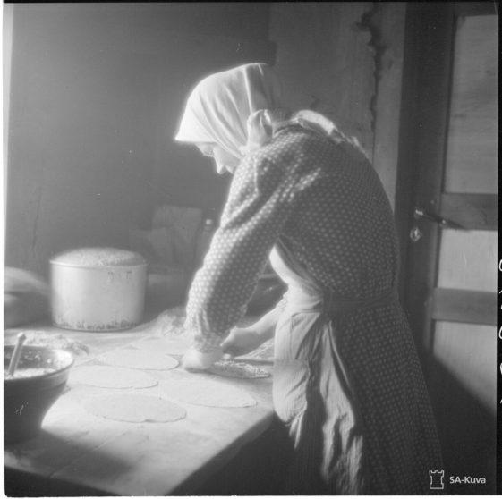 Nainen leipomassa piirakoita.
