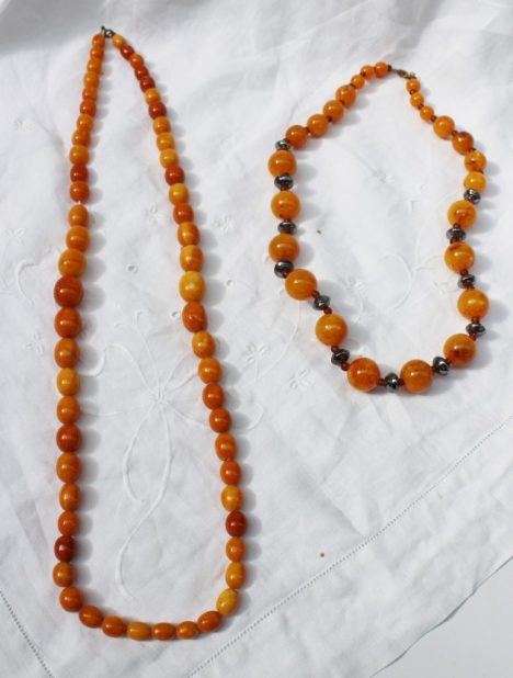 A single row necklace of sixty graduated oval amber beads approximately 67 grams, largest bead 18mm x 12mm, the smallest 10mm x 7mm together with another faux amber bead necklace with spherical beads. Sold for £830 at Anthemion Auctions