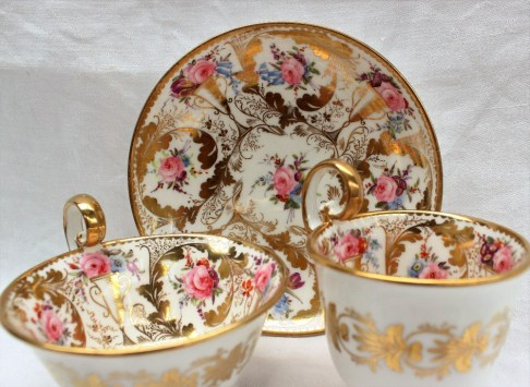 A Nantgarw porcelain trio, with a tea cup, coffee cup and saucer, each with a scalloped gilt rim, gilt swags and twin handled vases, painted with roses and other garden flowers. Sold for £1,050 at Anthemion Auctions