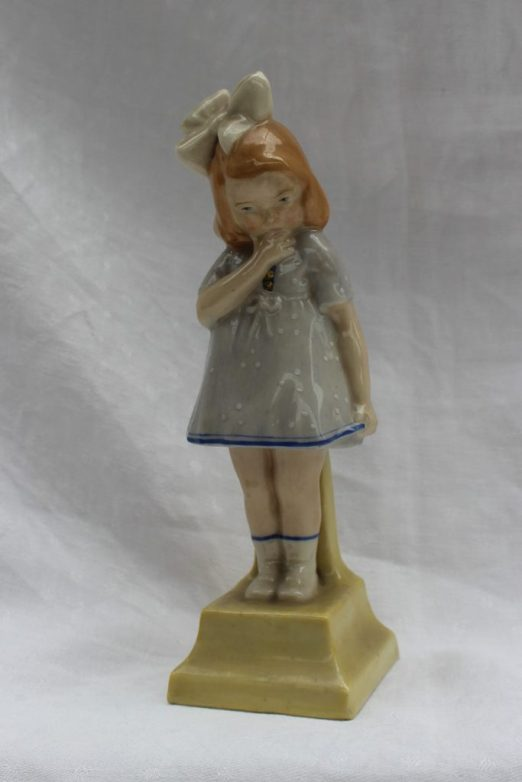 """A Royal Doulton figure - Shy Anne, HN65, in a pale blue dress with white dots, the bottom of the dress with blue line decoration, standing on a yellow plinth base, marked to the underside with a green printed mark, impressed 12.18 and painted 'Potted by:- Doulton & Co. """"Shy Anne."""" C.J. Noke. Sc., H.N.65.', 20cm high . Sold for £1,000 at Anthemion Auctions"""
