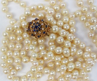 A long double string of pearls with 198 individually knotted regular spherical pearls each approximately 5mm in diameter to an 18ct yellow gold diamond and sapphire set clasp, approximately 116 grams. Sold for £720 at Anthemion Auctions