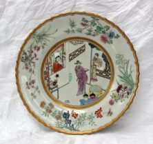 A Qing dynasty porcelain plate painted with an interior scene to the centre, the edge decorated with flowers, leaves and butterflies, to a gilt shaped rim, red seal mark to the reverse, 23cm diameter. Sold for £750 at Anthemion Auctions