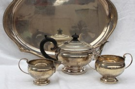 A George V silver three piece teaset, with a beaded rim, together with a matching twin handled silver tray, Birmingham, 1932 and a silver spoon, approximately 2064 grams. Sold for £550 at Anthemion Auctions
