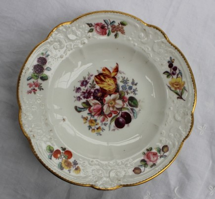"""A Nantgarw porcelain plate with a scalloped edge and moulded border painted with single flowers, painted to the centre with a spray of garden flowers, marked """"NANT- GARW C W"""". Sold for £600 at Anthemion Auctions"""