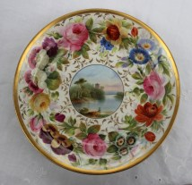A Swansea porcelain dish, the border profusely painted with roses, pansies and other garden flowers, the centre painted with a river scene in a circular vignette. Sold for £2,600 at Anthemion Auctions