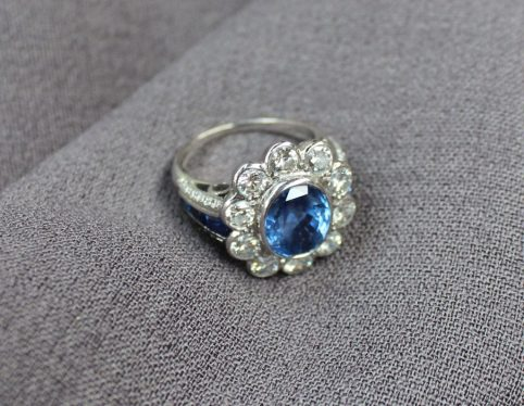 A sapphire and diamond cluster ring, the central sapphire measuring approximately 10mm by 8mm, surrounded by ten brilliant cut diamonds, each approximately 0.1 of a carat. Sold for £3,300 at Anthemion Auctions