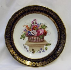 A Swansea porcelain dished plate decorated in the Lysaght pattern, painted with a basket of flowers on a pedestal, the royal blue border with gilt highlights, 20.3cm diameter, Sidney Heath collection label. Sold for £1,000 at Anthemion Auctions