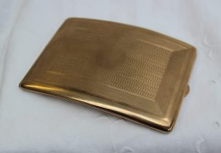 A 9ct yellow gold cigarette case of bowed form with engine turned decoration, approximately 148 grams. Sold for £990 at Anthemion Auctions