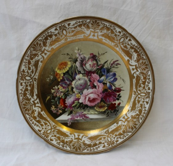 A 19th century porcelain plate with a shaped edge, the border with gilt decoration of leaves, sea creatures and stylised anthemions, the centre completely painted with a basket of garden flowers including tulips, roses etc, unmarked possibly Swansea, 21.3cm diameter . Sold for £1,800 at Anthemion Auctions