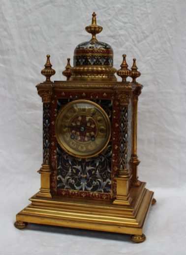 A 19th century gilt metal and champleve enamel decorated mantle clock, with a vase finial and dome , the four corners mounted with vases. Sold for £800 at Anthemion Auctions