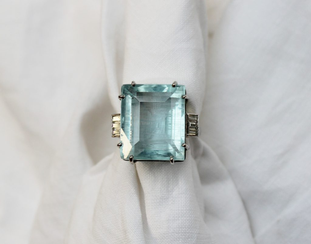 An Aquamarine and diamond dress ring the rectangular faceted aquamarine measuring 18mm x 15mm x 11mm deep, six claw set, the shoulders with six baguette cut diamonds to a white metal shank marked 18ct, size P. Sold for £880 at Anthemion Auctions