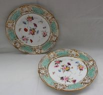 A pair of Nantgarw porcelain plates with a shaped edge moulded with scrolls, leaves and swags, with green jewelled decoration painted to the centre with sprays of garden flowers, impressed mark, 22cm diameter. Sold for £600 at Anthemion Auctions