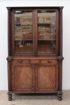 A Regency mahogany bookcase, the moulded cornice above a pair of glazed doors enclosed between rope twist columns, the base with a pair of faux drawers and two cupboards enclosed between rope twist columns on ball feet, 124cm wide x 209cm high x 54cm deep