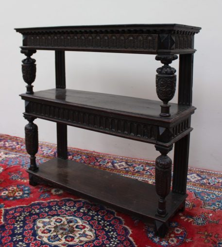 A 17th century and later oak three tier buffet, the rectangular moulded top above a carved frieze drawer, the central shelf with a carved drawer front and an undertier each section held aloft by carved cup and cover supports, 114.5cm wide x 112.5cm high x 38cm deep