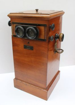 Lot 441 - Sold for £290 - The Myrioscope, a stereoscopic viewer in a mahogany case by Sanger-Shepherd & Co. Ltd, London, with a twin hinged top opaque glass panel to the reverse with mirror to the interior and glass photographic slides 23cm wide x 46cm high