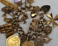 Lot 5 - Sold for £1,400 - A 9ct yellow gold charm bracelet, set with numerous charms including a chalet, chariot, Egyptian head, horse, car, 1895 half sovereign, stork, etc, overall approximately 124 grams