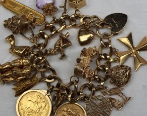 9ct yellow gold charm bracelet, set with numerous charms including a chalet, chariot, Egyptian head, horse, car, 1895 half sovereign, stork, etc, overall approximately 124 grams. Sold for £1,400 at Anthemion Auctions