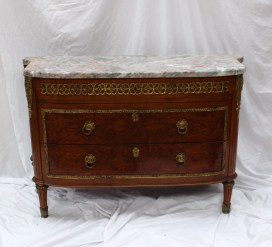 A continental marble topped commode, the shaped variegated marble top above a shallow drawer and two long drawers with gilt metal mounts on fluted tapering legs and leaf decorated feet, 125cm wide by 45cm deep. Sold for £1,150 at Anthemion Auctions