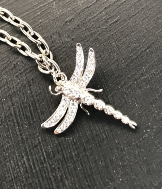 """A Tiffany & Co., platinum """"Dragonfly"""" charm bracelet, set with round brilliant cut diamonds, 0.12cts total weight, 15cm long, approximately 8 grams, boxed, plus additional links. The dragonfly is 2cm x 2cm, and each additional link is approximately 5mm long. Sold for £1,300 at Anthemion Auctions"""