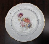 "A Nantgarw porcelain plate, with a C scroll border and dentil gilt rim, painted with a sprig of garden flowers to the centre with scattered butterflies, impressed ""NANT-GARW, C.W."" to the base, 25cm diameter. Sold for £1,200 at Anthemion Auctions"