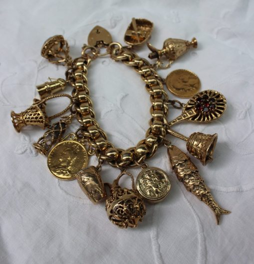 A 9ct yellow gold charm bracelet, set with numerous charms including a miners lamp, coracle, hand bell, reticulated fish, basket, coins etc, approximately 138 grams. Sold for £1,350 at Anthemion Auctions