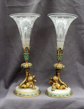A pair of 19th century champleve enamel decorated ormolu and etched glass cornucopia, the etched glass trumpet with an enamel mount held aloft by a winged cherub on a marble and enamel decorated base, 34cm high. Sold for £880 at Anthemion Auctions