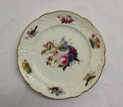 A Nantgarw porcelain plate with a scalloped gilt rim, painted with a spray of garden flowers to the centre, the moulded border painted with fruit and birds, impressed NANT-GARW C.W. mark, 21.5cm diameter. Sold for £850 at Anthemion Auctions