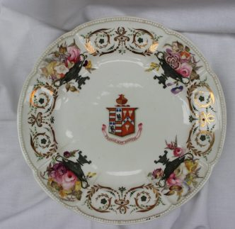 A Swansea porcelain dish, from the Clark of Hereford service, of cruciform shape, the rim individually applied with white beads, the centre painted with the arms of Clark of Hereford impaling Parkinson above the motto 'Frangas non Flectes', the border painted possibly by Henry Morris with garden flowers within green classical urns, alternating with green enamel and gold scrollwork, 23.7cm diameter, upper case mark in iron red ***A group of pieces from this important armorial service is illustrated by WD John, Swansea Porcelain (1958), pl. Sold for £1,100 at Anthemion Auctions